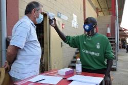Un integrant de l'organització del Club Futbol Montornès pren la temperatura a un espectador